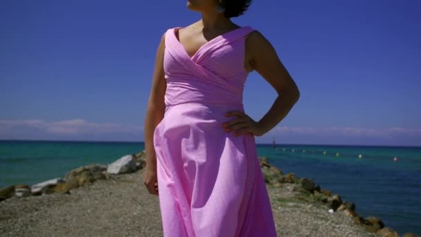 middle aged beautiful woman is posing on breakwater in sunny day, amazing picturesque sea horizon