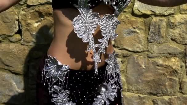 Frau trägt Kostüm mit leuchtenden Kristallen auf BH und Rock bewegt sich langsam im orientalischen Tanz