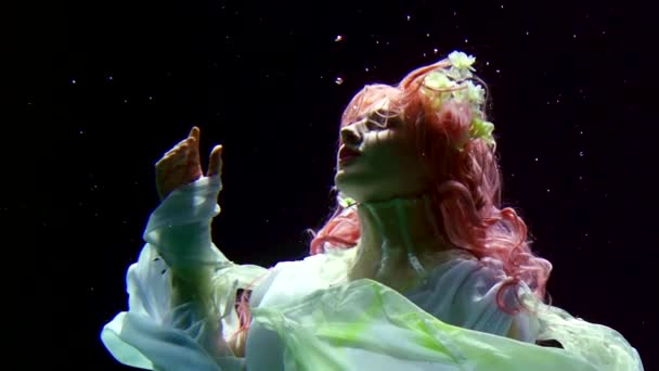 girl with pink hair and white dress swimming underwater on black background like in a fairy tale