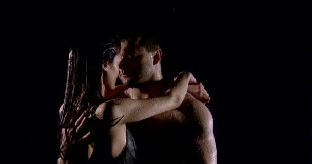 Nahaufnahme eines niedlichen jungen Paares in einer Beziehung, das im Dunkeln im Regen kuschelt. Nasse Menschen unter Wassertropfen