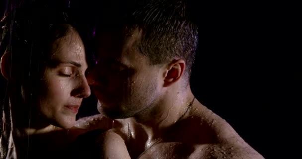 Porträt eines leidenschaftlichen schönen Paares mit nackten Schultern, die unter starkem Regen auf schwarzem Hintergrund sind.