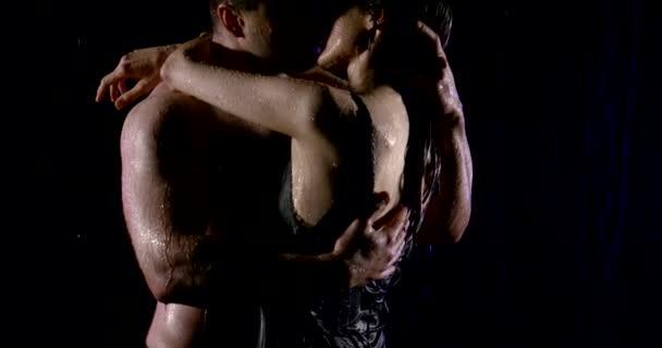 Egy izmos ember szenvedélyesen ölel, és megcsókolja a nőt a szakadó esőben egy fekete háttér közelről. Egy férfi egy meztelen törzs és egy nő egy fekete szűk ruhában. Szenvedély, érintés, csókolózás.