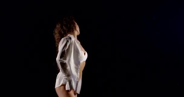 Krásná sexy dívka s dlouhými kudrnatými vlasy, bílými spodky a bílou košilí. Tančí na černém pozadí.