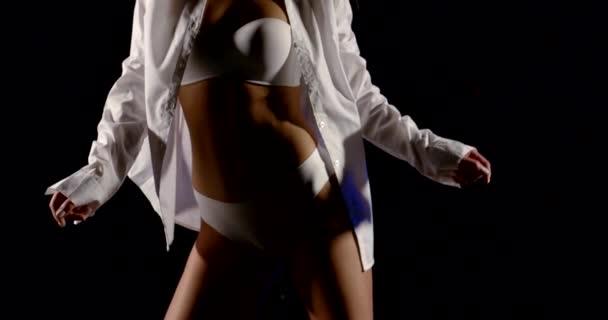 krásná postava dívky z bílého spodního prádla a bílé košile. Tančí na černém pozadí.