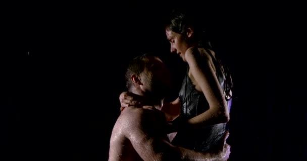 junger Mann und Frau streicheln unter Wasserströmen, Freund hält Mädchen