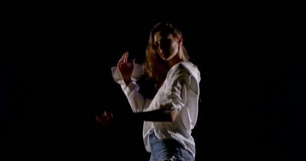 Bezstarostná mladá žena se volně pohybuje ve tmě, oblečená v bílé košili a džípi
