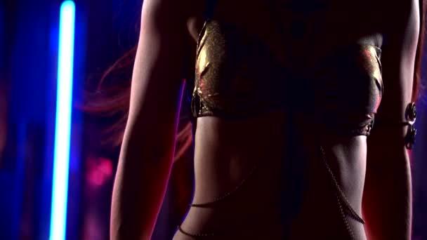 Nahaufnahme des Körpers einer schlanken, sexuellen Frau im Anzug zum Bauchtanz in der Dunkelheit