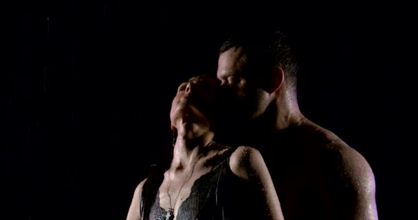 aufgeregten Frau genießt Umarmungen von starken muskulösen Mann unter Regen in der Dunkelheit