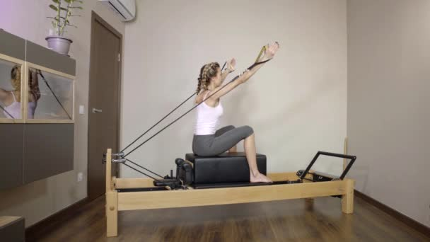 Athletic girl doing pilates exercise on a reformer machine.