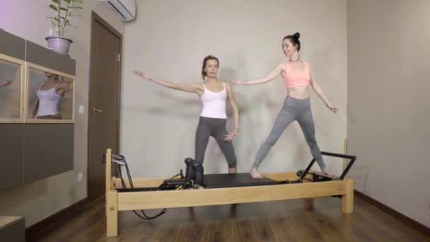 Fitness coach instructing woman on how to do exercise on a pilates reformer.