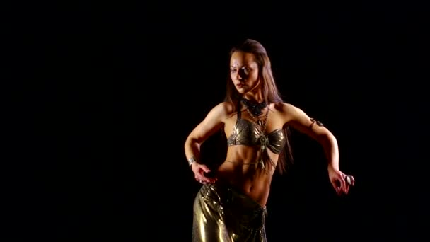 schlanke, athletische Frau tanzt orientalischen Tanz in Nationalkleidung in einem dunklen Raum