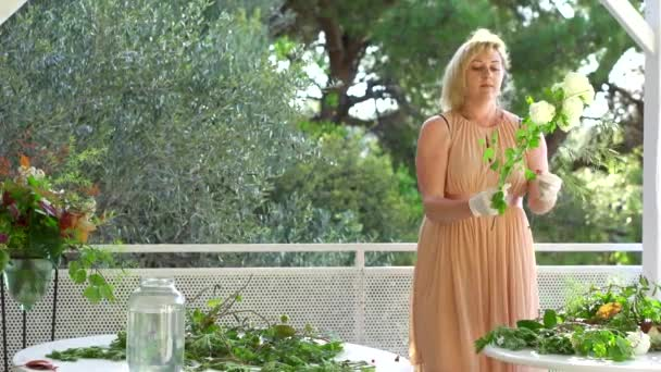 Charming blonde woman in a dress assembling lovely bouquet with summer flowers.