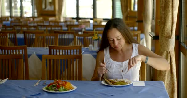 Frau in weißem Anzug isst Abendessen in leerem Restaurant