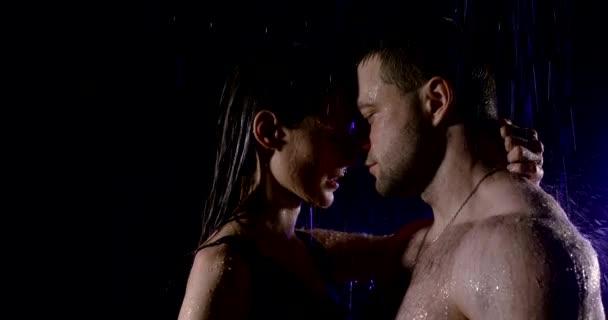Porträt Nahaufnahme in Profil leidenschaftlich, nass paar sind im Regen auf schwarzem Hintergrund. Sie umarmen sich, berühren sich, küssen sich, schauen sich an