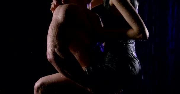 Junge, leidenschaftliche, nasse Paare sind im Regen auf schwarzem Hintergrund. Ein Mann hält eine Frau, sie umarmen und küssen.