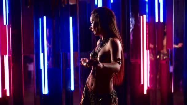 sexy Nahaufnahme Mädchen, das orientalischen Tanz auf einem hellen, bunten Hintergrund tanzt, sie ist in einem orientalischen Kostüm und wedelt mit Kopf und Haaren.