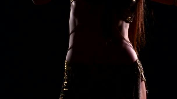 Hasa közelről egy szexi lány, aki táncol egy keleti tánc egy sötét háttér, ő visel keleti jelmez.
