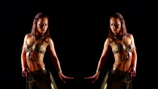 Nahaufnahme eines sexy orientalischen Mädchens, das orientalischen Bauchtanz auf dunklem Hintergrund tanzt. Es wird vom Licht erhellt. ein Video mit Reflexionseffekt.