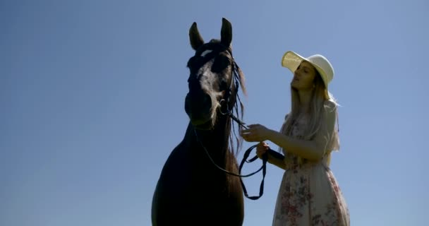 A slender blonde girl in a hat and a long dress stands against the blue sky and strokes a dark horse on the reins that stands next to her. They are outdoors on a summer day.