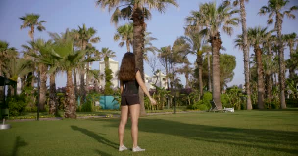 sexy brunette woman is squatting alone outdoors on nature of tropical city in morning, back view