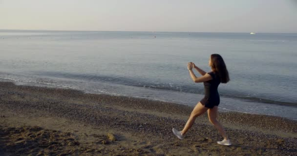 sportswoman is squatting alone near sea in daytime, training and doing exercises