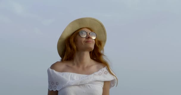 charming redhead woman is walking alone in summer day, tilt up view against blue sky