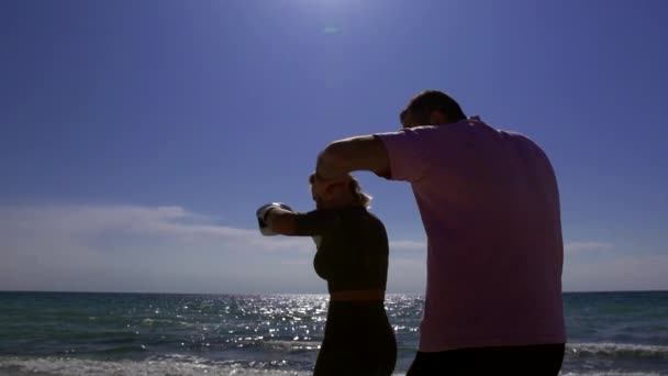 silhouette of two people against the sea. training punches the discipline of kickboxing. a man trains a woman