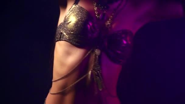 sinnliche Brünette Frau tanzt leidenschaftlich Bauchtanz in dunklen Raum, Detailansicht