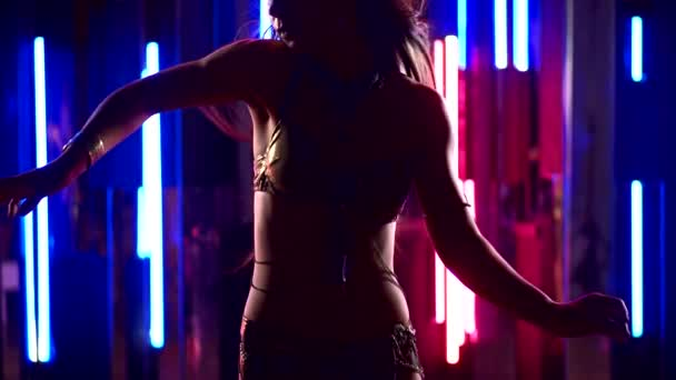 Silhouette einer Bauchtänzerin im Hintergrund von bunten Neonlichtern