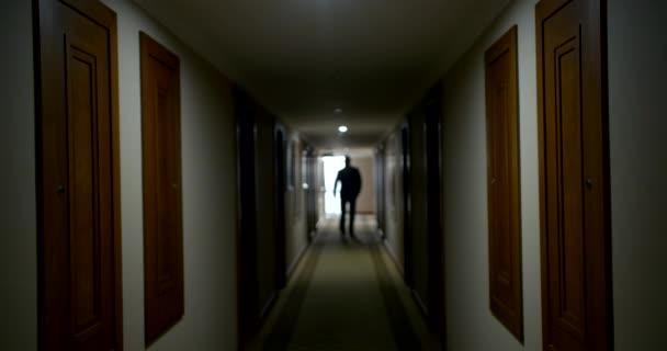 serious bald man silhouette walks along luxury hotel hall