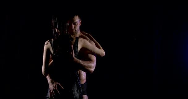 Aufgeregtes Liebespaar umarmt sich bei Regen in dunkler Straße, Mann streichelt Frauenkörper