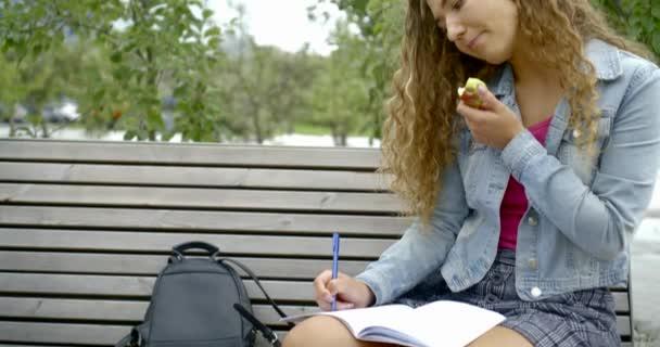 dívka píše v poznámkovém bloku pojídáním jablek na lavičce pomalý pohyb