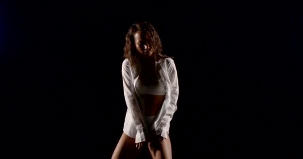 sexuální žena tančí ve tmě, nosí bílou košili a spodní prádlo