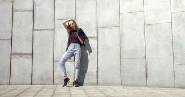 Teenagermädchen posiert an einem sonnigen Tag in der Stadt in der Nähe einer gefliesten Wand und hält ihre schwarze Jacke