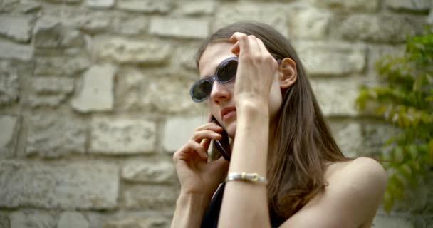 Portré közeli sötét hajú lány modell sötét ovális szemüveg állva, és beszél a telefonon, leveszi a szemüvegét, mosolyogva. Ez ellen egy kőfal.