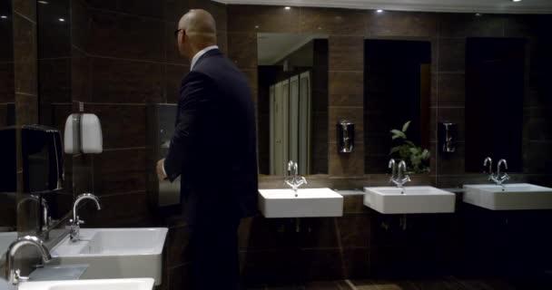 Üzletember egy öltönyt állva a fürdőszobában, és darabos kezét és arcát papírtörlő előtt a tükör és a mosogató