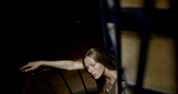 Portré egy fiatal lány, aki modell pózok támaszkodva korlát a lépcsőn a bejáratnál, felülnézet.