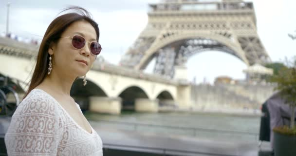 Close-up portrait of a dark-haired Asian middle-aged woman resting in Paris on the background of the bridge, the river Seine and the Eiffel tower. She has dark glasses on her face.