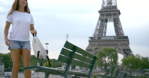 A dark-haired middle-aged woman walks with a backpack in her hand and sits on a bench against the background of the Eiffel tower in Paris. She smiles and shakes her hair. Slow motion.