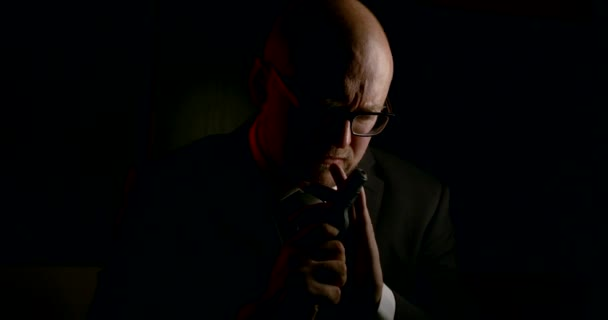adult bald gangster is holding gun and aiming in darkness