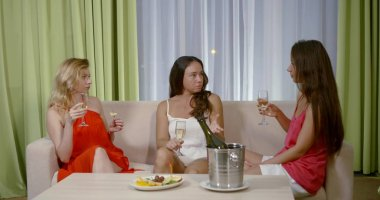 women communicate seriously on white sofa drinking champagne