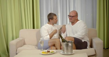 smiling gay couple drink champagne and communicate