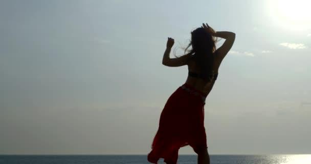 die Silhouette eines jungen langhaarigen schönen Mädchens, ein Blick von hinten, sie ist gegen Meer und Himmel, sie trägt ein Oberteil und einen langen östlichen Rock. Die Tänzer führen einen modernen Tanz auf.