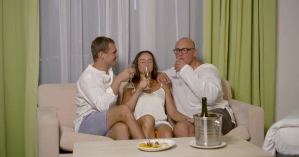ungewöhnliche Datum der Frau und zwei Männer im Hotelzimmer, sie trinken Champagner und flirten zusammen