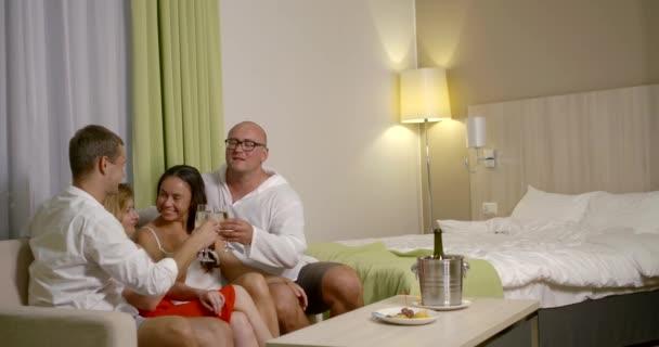 zwei verheiratete Paare tauschen Ehefrauen im Hotelzimmer, trinken Wein und plaudern fröhlich