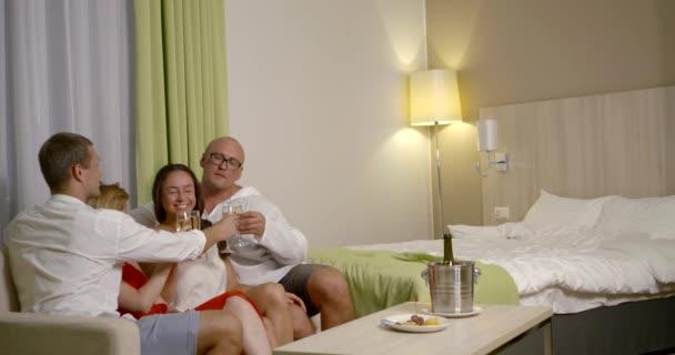 zwei erwachsene Paare im Hotelzimmer, Menschen sitzen auf der Couch und trinken Champagner