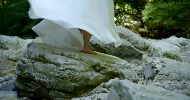 Frau wirbelt um sich herum auf Felsen, Nahaufnahme der Füße, sie trägt langen weißen Rock