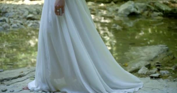 schlanke brünette Frau in traditioneller indischer Kleidung schlendert allein entlang des ruhigen Flusses im Wald