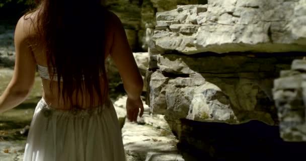 allein tanzende Frau wirbelt bei sonnigem Tag im Wald am Fluss mit den Hüften, Rückansicht