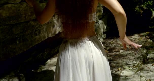 sexy junge Frau trägt langen weißen Rock läuft im Wald mit Steinen und schwenkt ihre Hüften